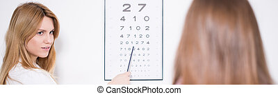 Ophthalmologist using Snellen chart to examine patient's...