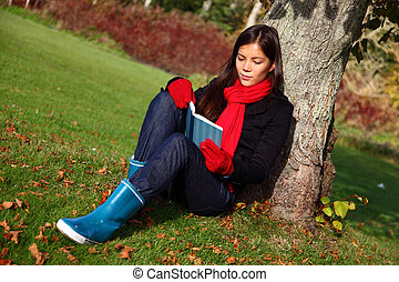 Reading under tree - Woman reading book outdoors in park...