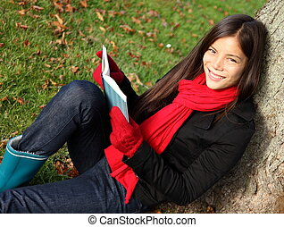 Woman reading book - Reading book and relaxing outdoors in...