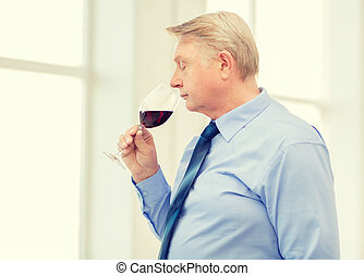 older man smelling red wine - alcohol and beverage concept -...