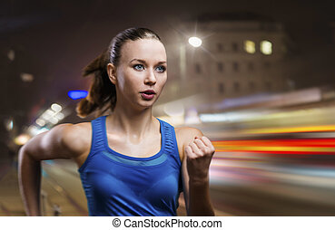 Jogging at night - Young woman jogging at night in the city