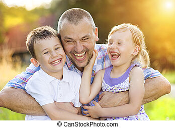 Happy family - Father with his two children spending time...