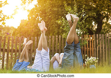 Happy family - Happy young family showing legs outside in...