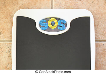 Bathroom scale with SOS text. Diet concept