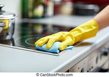 close up of woman cleaning cooker at home kitchen - people,...