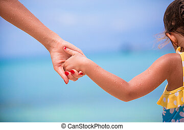 Trust family hands of child girl and mother on white beach