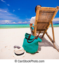 Young man relaxing in wooden chair on white sandy beach -...