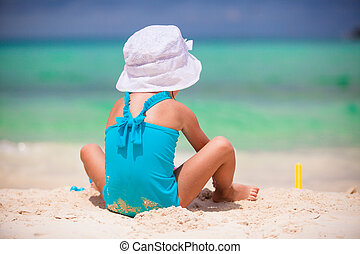 Adorable little girl playing with toys during beach vacation...