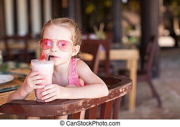 Adorable little girl having breakfast and drinking fruit...