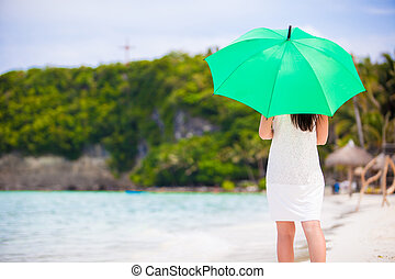 Young girl with green umbrella on white beach - Young woman...