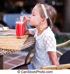Adorable little girl drinking fruit cocktail outdoor -...