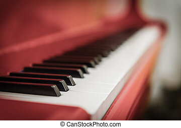 white and black keys of red piano closeup