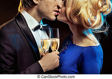 Kissing couple holding glases of a champagne - Kissing young...