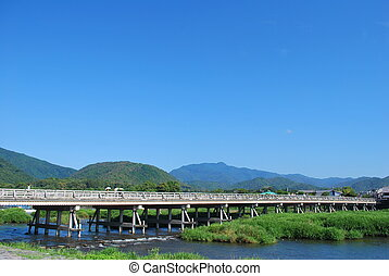 Huge, long bridge across a fast-flowing river - Huge, wooden...