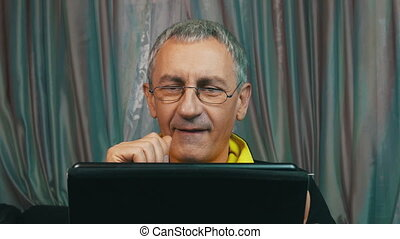 Portrait Smiling Man in Glasses Reading a Tablet Computer,...
