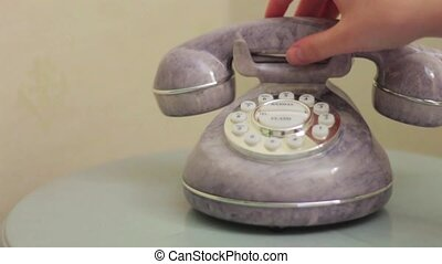 Lifting the telephone - Hand picks up an old phone, which...