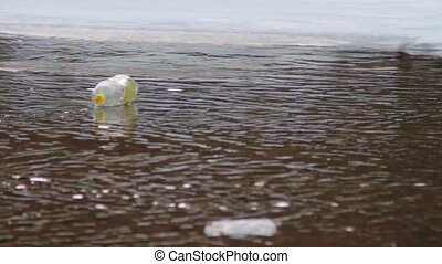 Plastic bottle floating in the mountain river Winter river