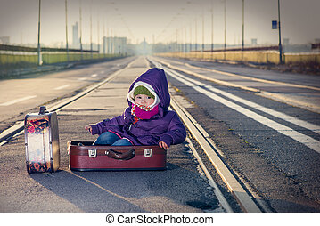 little girl sitting in a suitcase near the railway