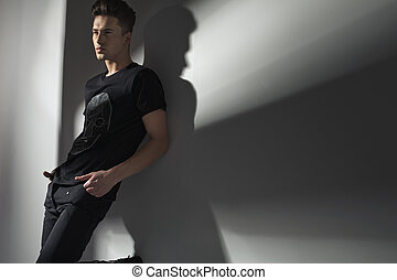 Attractive slim man leaning against the wall - Handsome slim...