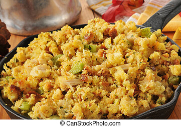 Cornbread stuffing with bits of turkey and celery in a cast...