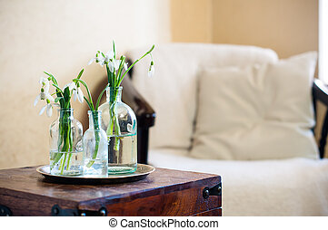 home interior - Spring flowers snowdrops in glass bottles,...