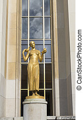 gold sculpture - statue of a woman in front of the cite de...