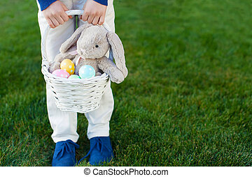 easter time - child holding basket with colorful easter eggs...