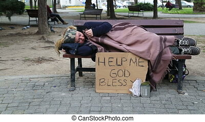Homeless woman resting on a park bench