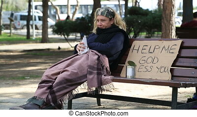 Homeless alcoholic woman drinking wine and coughing