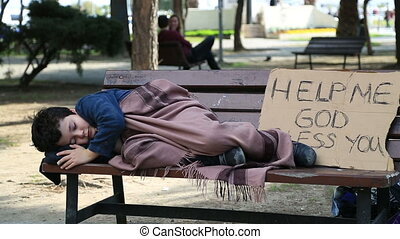 Homeless, tired child resting on a park bench