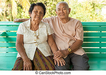 Happy Senior couple sitting indoor - Happy Asian Senior...