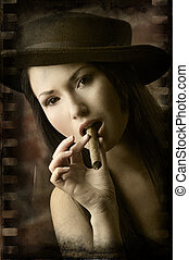 closeup of beauty chinese smoking cigar - portrait of pretty...