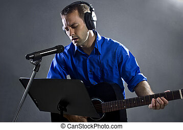 Male Guitar Player in Recording Studio - male singer holding...