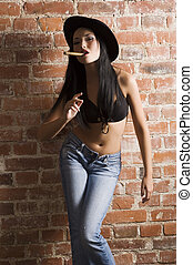 japanese smoking cigar - pretty asian girl against a brick...