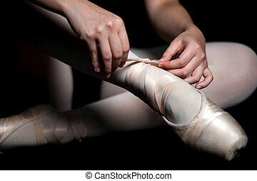 Ballet Slippers - A ballerina tying her ballet slippers on,...