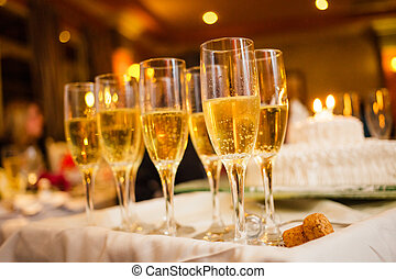 Many Champagne Glasses on a Tray with Anniversary Cake in...