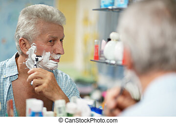 man shaving in bath - Portrait of a senior man shaving in...