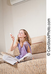 Young woman with phone - Cheerful young woman is sitting on...
