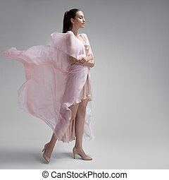 Beautiful woman in fluttering airy pink dress. Gray...