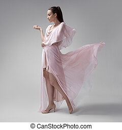 Beautiful woman in fluttering airy pink dress Gray...