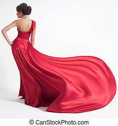 Young beauty woman in fluttering red dress. White...