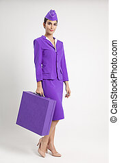 Charming Stewardess Dressed In Violet Uniform And Suitcase