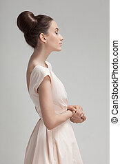 Beautiful woman in pink retro dress. Gray background.
