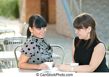 Coffee break - Two friends having coffee break in street...