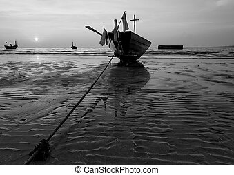 The fishing boat stuck on sand beach in black and white ,...