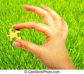 gold puzzle - woman fingers holdings gold puzzle on lawn