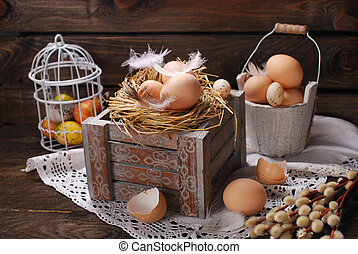 rustic still life with eggs in nest on wooden box for easter...