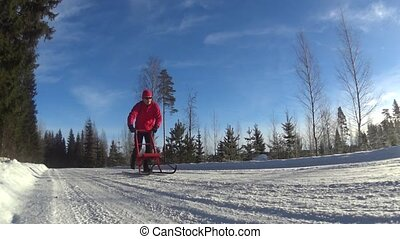 Man riding kicksledge on road - Man riding kicksledge on...