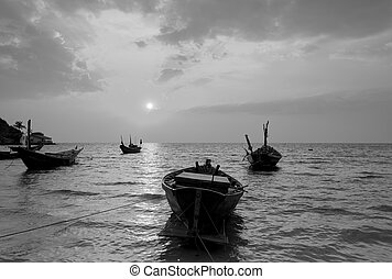 The fishing boat with a beautiful sunset in black and white,...