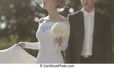 Slender young bride circling the park and kisses the groom -...